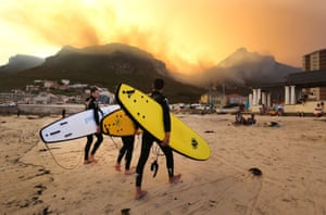 Surfers walk on the beach while the fire continues to blaze on the mountains behind them in Cape Town