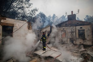 A fire fighter extinguishes the remains of a home in Tokai