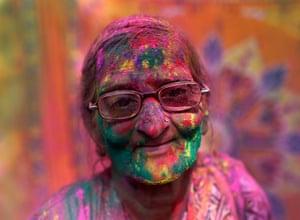 A widow daubed in colours takes part in Holi at Vrindavan ,in Uttar Pradesh