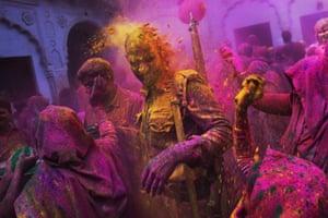 Widows at an ashram throw coloured powder at a police officer in Vrindavan