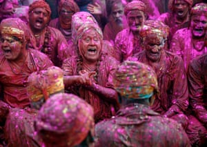Men sing provocative songs to gain the attention of women as they celebrate Lathmar Holi in Nandgaon