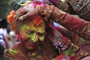 People cover a girl's face with coloured powder as they celebrate in Kolkata