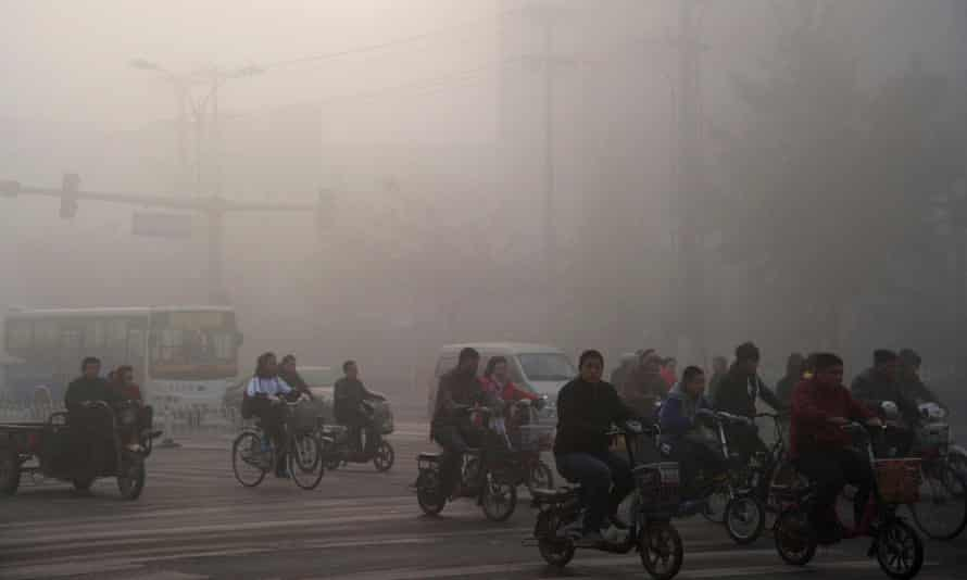 People cycle through the haze-filled streets in Xingtai, Hebei province, China