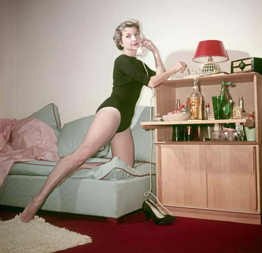 A woman in bodysuit and fishnet stockings posing leaning on a cocktail cabinet with a telephone in the hands. 1950s
