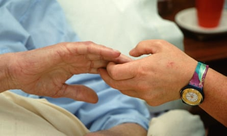 Hospice worker holding the hand of an elderly man