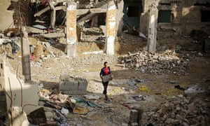 A Palestinian young man amid the rubble of destroyed buildings in the Gaza Strip