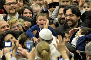 Pope Francis touches a child's face in Vatican City, Italy