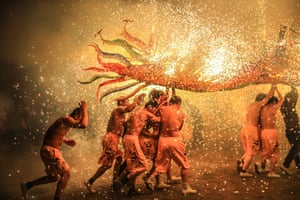 Villagers perform a 'dragon dance' as fireworks are set off in China