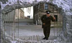 An East German border guard looks through a hole in the Berlin Wall on 19 November 1989.