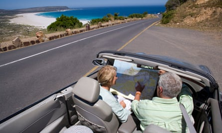 An older couple in a convertible car