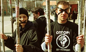 Otpor members protest in a mock cage.