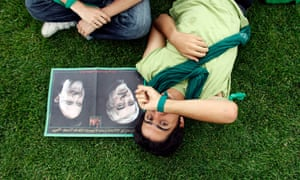 A supporter of Mir Hossein Mousavi rests by photos of the former prime minister and former president, Mohammad Khatami during a pre-election rally in Karaj.