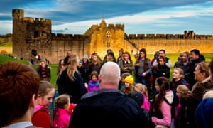 Tour guide and group of visitors on Harry Potter theme tour of Alnwick Castle.