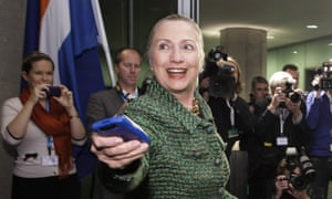 In a 2011 photo, then-Secretary of State Hillary Clinton hands off her mobile phone in The Hague, Netherlands.