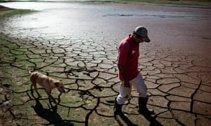 A resident walks with a dog across the drying bottom of the Paraibuna dam in Redencao da Serra