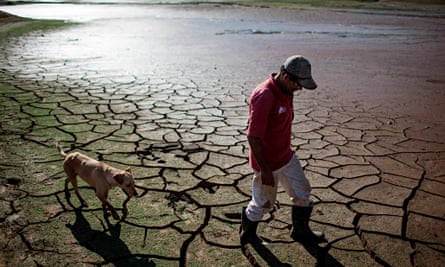A resident walks with a dog across the drying bottom of the Paraibuna dam in Redencao da Serra