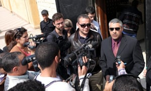 Al-Jazeera journalists Mohammed Fahmy (right) and Baher Mahmoud (left) speak to reporters outside a courthouse after their trial session in Cairo where prosecution witnesses failed to appear.