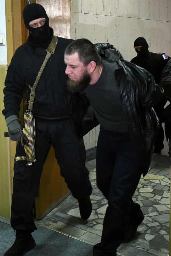 Tamerlan Eskerkhanov is taken into court by a policeman. Esterkhanov said he was at work at the time of Nemtsov's murder and had witnesses who could prove it.