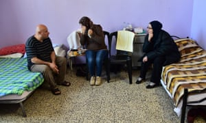 Syrian migrants sit on beds at a refugee centre in Milan, Italy