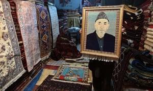 A Kabul trader displays a carpet bearing the image of former president Hamid Karzai.