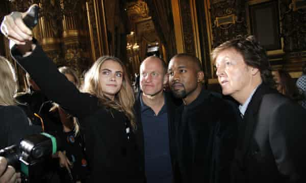 Cara Delevingne, takes a photographer with Woody Harrelson, Kanye West and Paul McCartney prior to the Stella McCartney show.