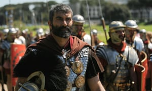 Men dressed as ancient Roman soldiers march through Circus Maximus.