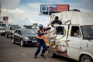 A traffic policeman has an altercation with a passenger in a van who is half hanging out of the side door of the vehicle. Crucially, for the corruption-weary road users of Kinshasa, the robots don't take bribes