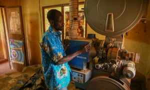 Projectionist Antoine Oudraogo next to an old film projector at the Cinéma Somgande during the festival.