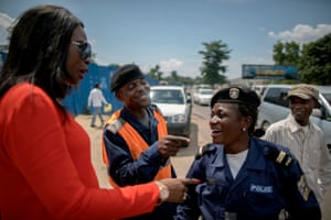 "Therese Izay, left, speaks to traffic police officers in the city. While Kinshasa's chief of police welcomed the introduction of the robots at notorious junctions, <a href=""http://www.citylab.com/tech/2015/03/the-case-against-giant-traffic-robots/387358/"">critics suggest</a> that the traffic-bots are simply an 'eye-catching distraction' from a lack of infrastructure planning"