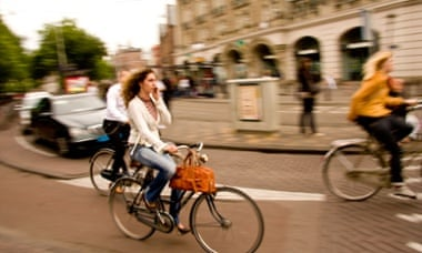 A woman talks on phone while cycling in Amsterdam, a city known for its dedicated bike lanes and the best cycling infrastructure in the world. Photograph: Alamy