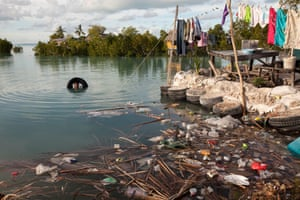 A boy swims next to his house in Temwaiku. Pollution is a huge issue in South Tarawa with virtually non-existent hard waste management, and here more rubbish is deposited with the tide each day.