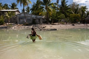 A young girl crosses the lagoon at high tide to get some water for her family, who live on a thin strip of sand that gets cut off from the main island every high tide.