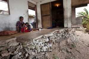 26. Jondrick Joash, 54, and her granddaughters Nola and Judy live in their half demolished house in Utidrikan, Majuro. The front rooms and kitchen were washed away in February 2014, leaving just the front door, one tiny bedroom and a narrow strip of concrete that falls away to the eroded shore below. Eleven people live in the cramped ruin.