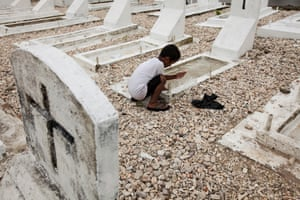 A young boy scoops water out of the graves in Demon Town, Majuro. Many graves in this cemetery have been relocated further inland after washed into the sea during storms that coincided with a high tide in 2013. But after only being moved around 10 metres inland, the sea is already threatening to take these graves too.