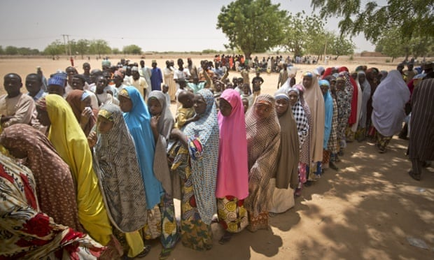 Nigerian women queue to cast their votes in the midday sun at a polling station in Daura.