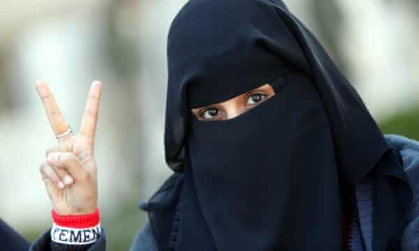 A female Yemeni student living in Iran flashes the victory sign during a protest against Saudi-led airstrikes.