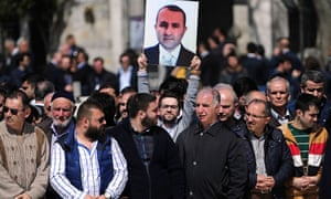 A man holds a portrait of killed prosecutor Mehmet Selim Kiraz during a funeral ceremony outside the Eyup Sultan Mosque in Istanbul.