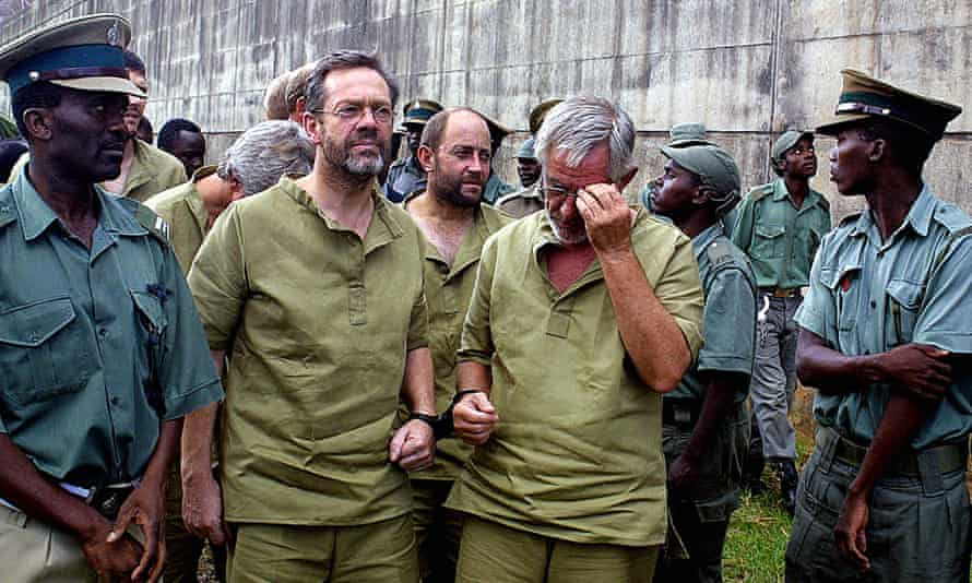 Simon Mann, left, the leader of a group of foreign mercenaries, leaves court in Harare in March 2003