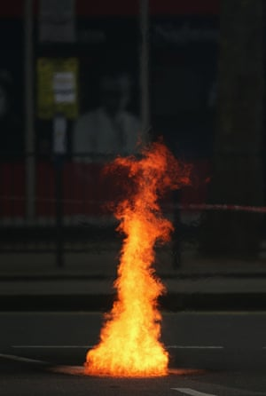 Flames pour out of a manhole cover.