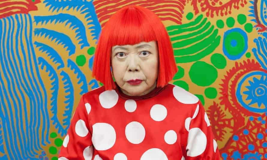Yayoi Kusama sits in front of one of her newly finished paintings in her studio.