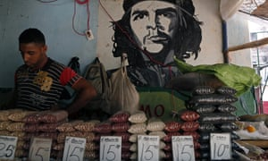 A man works at a bean stall at a market beside a mural with the a picture of revolution hero Ernesto 'Che' Guevara in Havana, Cuba.