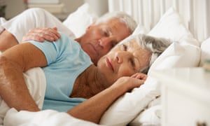 Older woman awake in bed with her husband (posed by models)