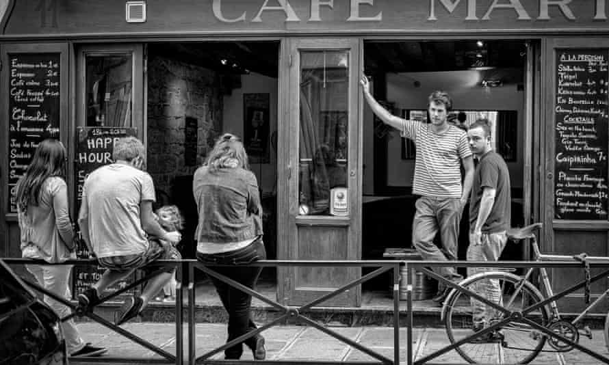 People on the street outside of a French cafe