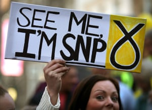 An activist holds a sign as SNP leader and first minister Nicola Sturgeon campaigns in Stirling.