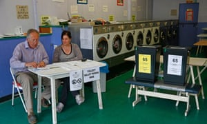Poll clerks wait for voters in a public launderette being used as a polling station in Oxford.