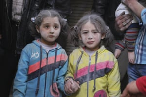 Girls hold hands in Aleppo, Syria, after surviving what activists said was a ground-to-ground missile attack by forces loyal to president Bashar al-Assad
