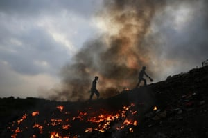 Impoverished Indians walk next to burning rubbish at Dharavi, one of the world's largest slums, in Mumbai. Air pollution kills more than 627,000 people in the country, according to the World Health Organisation. It puts 13 Indian cities in the world's 20 most polluted