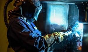 A welder works on a part of a JCB telescopic handler.