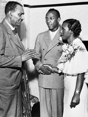 1935 Jesse Owens, record-breaking track star of Ohio State University, was married a few hours after he arrived in Cleveland from Chicago, to his Cleveland sweetheart, Minnie Ruth Solomon. Photo shows the Rev. Ernest Hall of the East Mount Zion Baptist Church, performing the ceremony at the home of the Bride