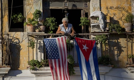 Javier Yanez stands on his balcony where he hung a U.S. and Cuban flag in Old Havana Cuba